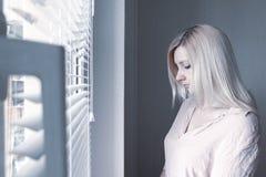 Droevige apathische eenzame vrouw die door een venster thuis of hotel, scheidings, depressie en apathieconcept kijken royalty-vrije stock foto