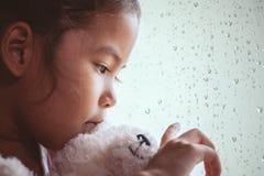 Droevige Aziaat weinig haar pop koesteren en kindmeisje die buiten kijken stock foto's