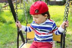 Droevige babyjongen op schommeling Stock Afbeeldingen
