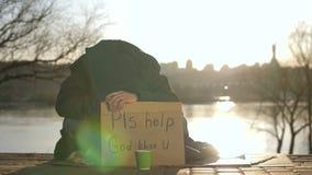 Droevige bedelaarszitting met hoofd die neer om hulp vragen stock video