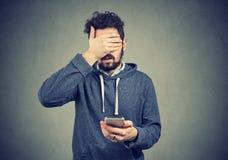 Droevige bedroevende jonge mens met mobiele telefoon royalty-vrije stock afbeeldingen