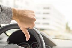 Droevige bestuurder die duimen in auto tonen Ontevreden mens royalty-vrije stock foto