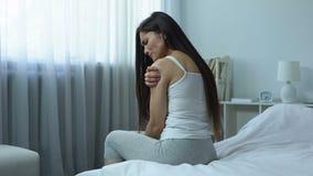 Droevige dame die kramp en pijn in schouder voelen, die spieren, verwonding proberen uit te rekken stock video