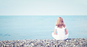 Droevige eenzame jonge mooie vrouwenzitting terug op strand het overzees Royalty-vrije Stock Afbeeldingen