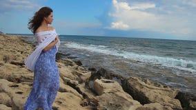 Droevige eenzame jonge vrouw die stormachtige overzees, golven bekijken die, rotsachtige kust, wind bespatten stock footage