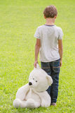 Droevige eenzame jongen met teddybeer die zich in de weide bevinden Kind die neer kijken Achter mening Droefheid, vrees, eenzaamh stock afbeeldingen