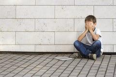 Droevige, eenzame, ongelukkige, teleurgestelde kindzitting alleen op de grond De jongen die zijn hoofd houden, kijkt neer Tabletp Royalty-vrije Stock Fotografie