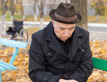 Droevige eenzame oude mens op een parkbank Stock Afbeelding