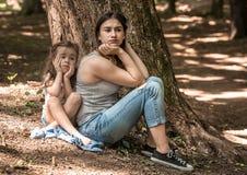 Droevige emoties van een meisje met haar moeder stock afbeelding