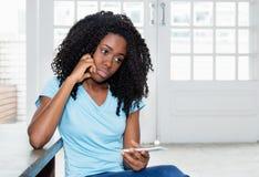 Droevige en eenzame Afrikaanse Amerikaanse vrouw die op bericht wachten stock fotografie