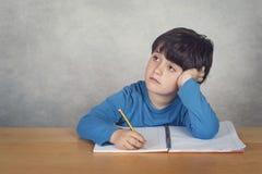 droevige en peinzende jongen met een boek op een lijst Stock Afbeeldingen
