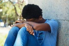 Droevige en slechte Afrikaanse jonge volwassene in openlucht royalty-vrije stock afbeeldingen