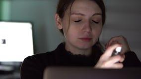 Droevige en vermoeide vrouw die met PPD naast lijst, die aan laptop werken eruit zien stock footage