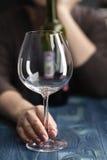 Droevige en verspilde alcoholische vrouwenzitting die thuis rode wijn drinken stock afbeeldingen