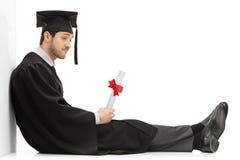 Droevige gediplomeerde student met een diplomazitting op de vloer stock fotografie