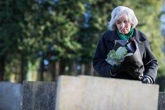 Droevige Hogere Vrouw met Bloemen die zich door Graf bevinden royalty-vrije stock afbeeldingen