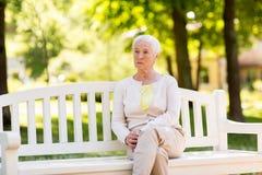 Droevige hogere vrouwenzitting op bank bij de zomerpark royalty-vrije stock afbeelding