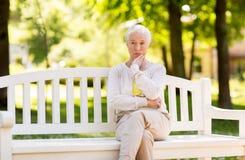 Droevige hogere vrouwenzitting op bank bij de zomerpark royalty-vrije stock fotografie