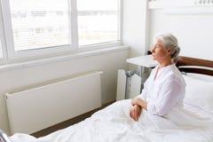 Droevige hogere vrouwenzitting op bed bij het ziekenhuisafdeling stock afbeeldingen