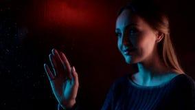 Droevige jonge dromerige vrouw dichtbij vochtig glasvenster wat betreft tekeningshart in het blauwe neonlicht en kindmeisje achte stock videobeelden