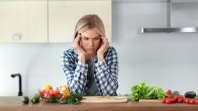 Droevige jonge huisvrouw die hoofdpijn hebben tijdens kokende gezonde verse salade bij keuken stock video