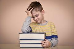 Droevige jonge jongen en boeken Royalty-vrije Stock Afbeeldingen