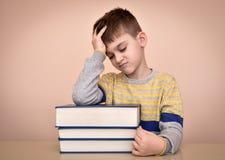 Droevige jonge jongen en boeken Stock Foto