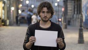 Droevige jonge mens die een whitecopy ruimtebanner op de straat houden stock videobeelden