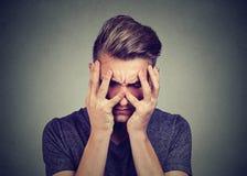 Droevige jonge mens die neer kijken Depressie en bezorgdheidswanordeconcept Stock Afbeelding