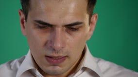 Droevige jonge mens die, op een groene achtergrond van de het schermstudio beginnen te schreeuwen Sluit omhoog stock footage