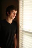 Droevige jonge mens die uit venster kijkt royalty-vrije stock afbeelding