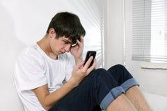 Droevige Jonge Mens met Cellphone Stock Foto