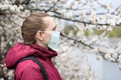 Droevige jonge vrouw in beschermend medisch gezichtsmasker Bloeiende boom op achtergrond De lenteallergie royalty-vrije stock afbeeldingen