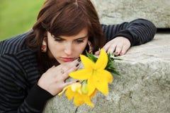 Droevige jonge vrouw die op de grafsteen liggen Stock Foto's