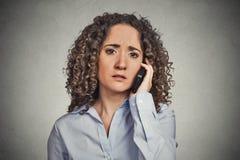 Droevige jonge vrouw die op mobiele telefoon spreken Stock Afbeelding