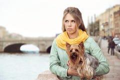 Droevige jonge vrouw met kleine hond op embarkment, wachtende vriend Stock Afbeeldingen