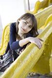Droevige jonge vrouwenzitting op gele bank Royalty-vrije Stock Fotografie