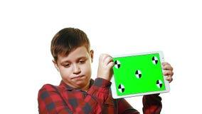 Droevige jongen die een tablet in zijn hand met het groen scherm houden stock video
