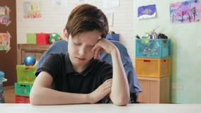 Droevige jongen die slaperige zitting voelen bij het bureau in zijn ruimte stock footage