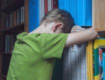 Droevige jongen die tegen een boekenkast leunen stock fotografie