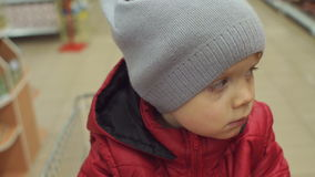 Droevige jongen met een vuil gezicht in het winkelen karretje stock videobeelden