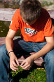 Droevige jongen op parkbank stock fotografie