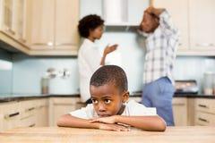 Droevige jongen tegen ouders het debatteren Stock Afbeeldingen