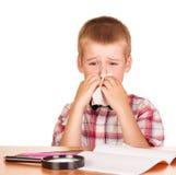 Droevige jongenszitting bij lijst, notitieboekje, potloden, geïsoleerd vergrootglas Stock Afbeelding