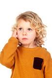 Droevige kleine jongen die zijn hoofd krassen Royalty-vrije Stock Afbeeldingen