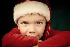 Droevige kleine jongen in santahoed Stock Afbeeldingen