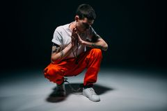 Droevige mannelijke gevangene die in oranje broek en manchetten rozentuin en het bidden houden royalty-vrije stock foto