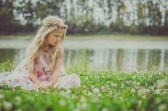 Droevige meisjeszitting alleen in het gras door de rivier Royalty-vrije Stock Foto