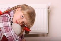 Droevige meisjeszitting dichtbij verwarmer. Het probleem van kinderen. stock fotografie