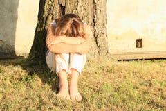 Droevige meisjeszitting door boomstam stock foto